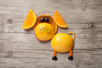 Funny pig made of orange and grape on wooden background