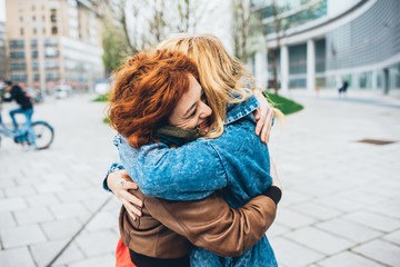 Two friends redhead and blonde girl meeting in the street of the city and hugging –friendship, happiness concept