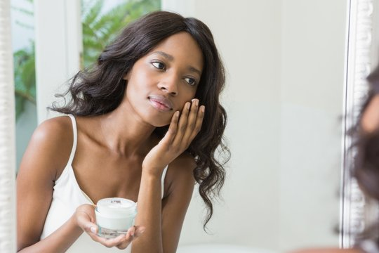 Young african american woman applying moisturizer