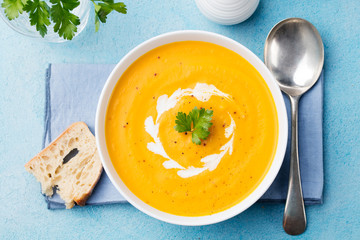 Pumpkin and carrot soup with cream and parsley on blue stone background Top view.