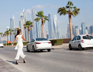 Beautiful fashion young woman walking on the Dubai street.