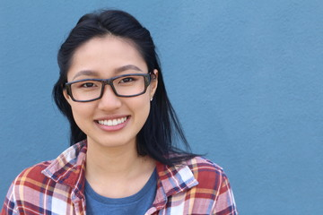 Portrait of beautiful Asian teen girl smiling, with wayfarers, isolated on blue background with copy space on the right of the image