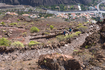 Hiker on the trail from the Valle Gran Rey to the village Arure in the highlands of the Canary island on La Gomera. 850m up on serpentine to the La Merica plateau on top of the mountain
