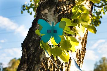 Голубая бабочка с лентой из бумаги на траве