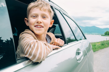 Happy boy look out from window car