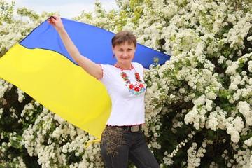 Девушка с флагом Украины на фоне цветущего кустарника
