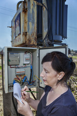 Woman technician inspecting electric meter reading  in distribut