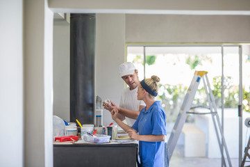 Side view of couple standing at kitchen counter covered in decorating equipment