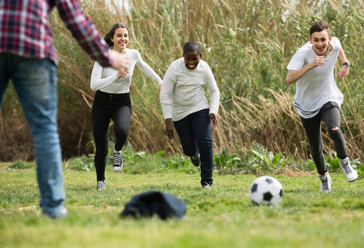 girl and three boys playing football in spring park and smiling
