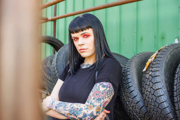 Tattooed woman leaning against tyres arms crossed looking at camera