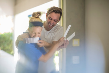 Couple holding paint swatches fooling around laughing