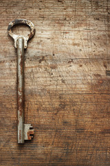 Old metal key on wooden background