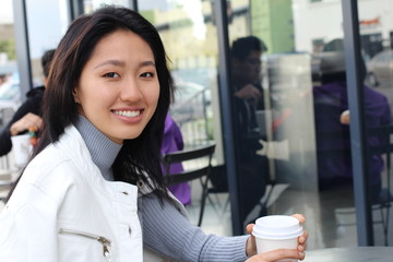 Young natural Asian woman sitting next to windows in cafe.