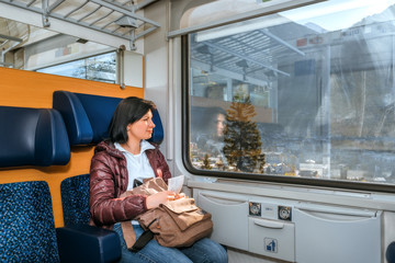 Girl riding on a train with a backpack and tickets. Traveling by train at the Alpine Railroad.
