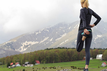 Female runner stretching legs after workout exercising in beautiful nature mountain landscape.