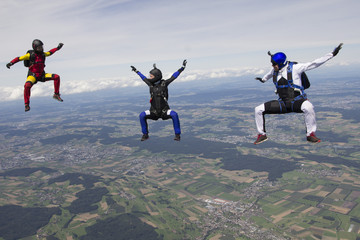 Team of three skydivers in sit fly position over Buttwil, Luzern, Switzerland
