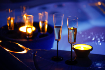 Candlelit champagne glasses beside a jacuzzi