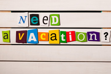 Need a vacation - written with color magazine letter clippings on wooden board
