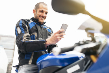 Handsome biker using mobile phone.