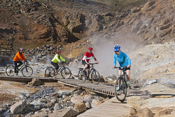 Four cyclists riding hybrid bikes at geothermal site, Krysuvik, Reykjanes, Iceland
