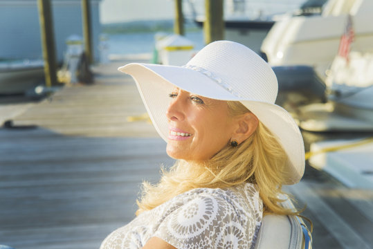 Mature woman sitting on harbor pier, Monmouth Beach, New Jersey, USA
