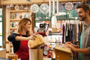 Female shop assistant packing bread for shopper in health food store