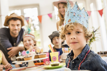 Portrait of boy wearing party hat at birthday party