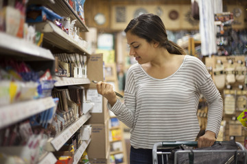 Young woman examining product in health food store