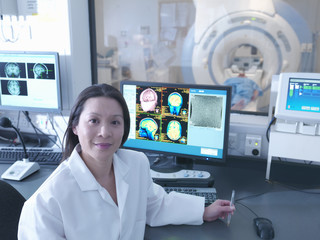 Scientist with Magnetic Resonance Imaging (MRI) 3 Tesla twin speed scanner, portrait
