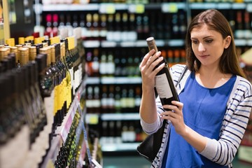 Woman looking at wine bottle