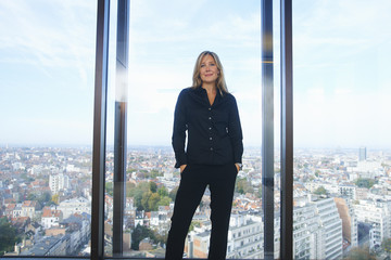 Portrait of  businesswoman in front of office window with Brussels cityscape, Belgium