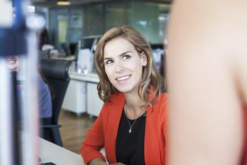Two businesswomen having informal meeting at office desk