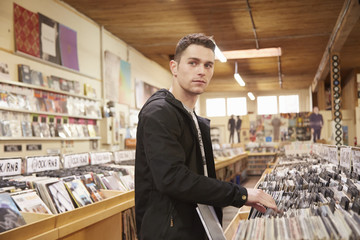 Young man browsing vinyl records in music store