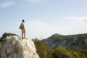 Male hiker on top of rock looking out at landscape, Sardinia, Italy