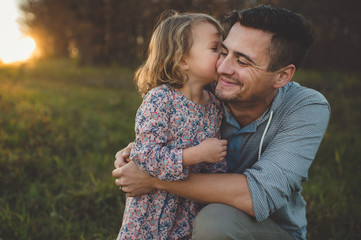 Girl kissing father on cheek in field