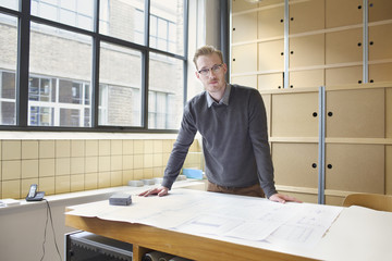 Portrait of young male designer in creative office