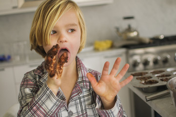 Portrait of boy licking chocolate cake mixture from fingers