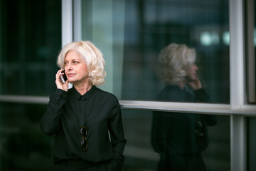 Mature businesswoman, standing outside building, using mobile phone