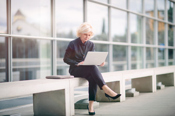 Mature businesswoman, sitting on bench, outside building, using laptop