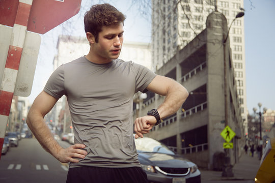 Young male runner checking wristwatch, Pioneer Square, Seattle, USA