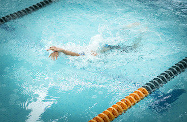 Young athletic man with butterfly swimming technique.