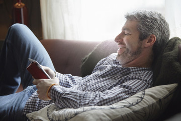 Young man reclining on living room sofa using digital tablet