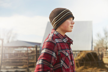 Portrait of boy wearing knit hat in dairy farm yard