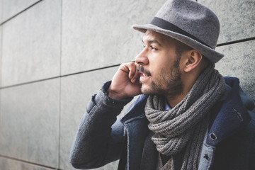 Close up of businessman leaning against wall talking on smartphone
