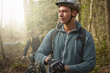 Two young men in forest, riding mountain bikes