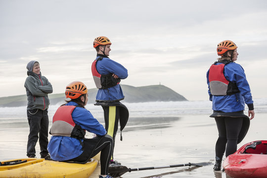 Four people on beach with kayaks, Polzeath, Cornwall, England