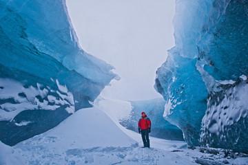 Mature man standing next to pile of snow exploring crystal ice cave, Breidamerkurjokull, Vatnajokull, Iceland