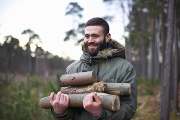 Young man collecting logs for campfire in forest