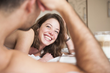 Over shoulder view of young couple laughing in bed