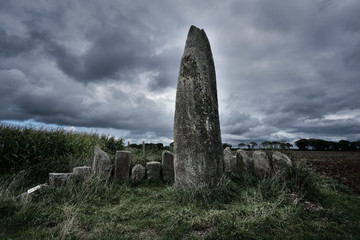 View of Menhir de Prat Ledan with dramatic gray clouds in Brittany, France Wall mural